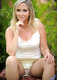 Intoxicating milf takes off some clothing in her garden